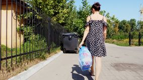 Back view, girl is carrying a package of garbage in her hands, throwing out trash. summer hot day. ecology. separation