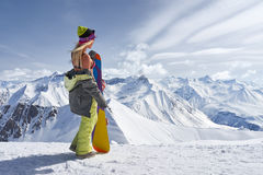 Back view of girl with colorful snowboard looking away mountains Stock Photos