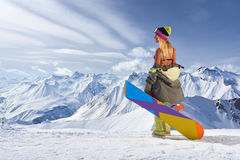 Back view of girl with colorful snowboard looking away mountains Royalty Free Stock Photography