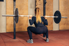 Back view girl doing heavy squat with barbell Royalty Free Stock Images