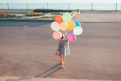 Cheerful girl holding colorful balloons and childish suitcase wa. Back view of girl holding colorful balloons and childish suitcase walking  in the city park on Royalty Free Stock Images