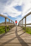 Back view of girl running in a wood boardwalk Royalty Free Stock Photos