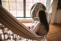 Back view of a girl sitting in a hammock in a cozy room with wooden floor and panoramic windows and a round mirror on royalty free stock photo