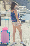 Back view girl is sitting with pink suitcase Stock Photo