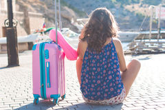 Back view girl is sitting with pink suitcase Stock Image