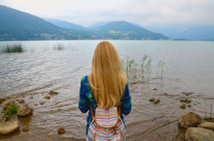 Back view of girl standing near water and looking at horizon with mountains stock photo