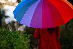 Back view of girl with umbrella. Beautiful young girl taking a midday walk through a city park wearing a bright red coat with a colorful umbrella Royalty Free Stock Photography