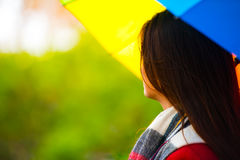 Back view of girl with umbrella. Beautiful young girl taking a midday walk through a city park wearing a bright red coat with a colorful umbrella Royalty Free Stock Images