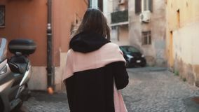 Back view of girl walking alone in old town. Brunette woman going through the street. Female have vacation in Europe. Back view of brunette girl with pink scarf stock video footage