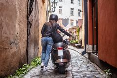 Back view of a girl walking with a scooter along the old narrow streets of Latvia. royalty free stock image