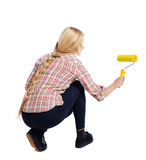 Back view of a girl who paints the paint roller. Stock Photo