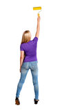 Back view of a girl who paints the paint roller. Royalty Free Stock Photo