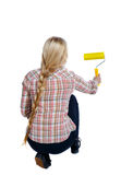 Back view of a girl who paints the paint roller. rear view people collection. Backside view of person. Isolated over white background. girl smears the wall Royalty Free Stock Photo