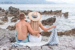 Back view of girlfriend and boyfriend. Sitting on rocky beach in Montenegro stock photos
