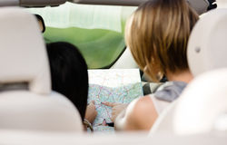 Back view of girls with the highway map in the car Royalty Free Stock Images