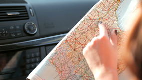Back view of girls studying the map while traveling by car stock video