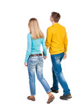 Back view going couple. walking friendly girl and guy holding h Royalty Free Stock Photos