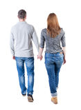Back view going couple. walking friendly girl and guy holding h Stock Images