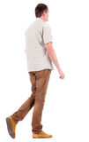 Back view of going  handsome man in brown jeans and a shirt. Stock Photos
