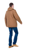 Back view of going  handsome man in brown parka. Stock Photography