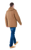 Back view of going  handsome man in brown parka. Stock Photo