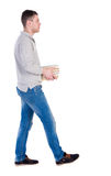 Back view of going  handsome man carries a stack of books. Walking young guy . Rear view people collection.  backside view of person.  Isolated over white Royalty Free Stock Photography