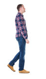 Back view of going  handsome man in checkered shirt. Royalty Free Stock Images