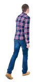 Back view of going  handsome man in checkered shirt. Stock Photos