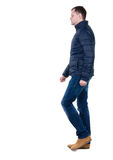 Back view of going  handsome man in jeans and jacket. Royalty Free Stock Photo