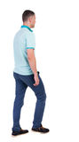 Back view of going  handsome man in jeans and a shirt. Stock Photography