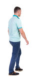 Back view of going  handsome man in jeans and a shirt. Royalty Free Stock Photo
