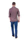 Back view of going  handsome man in jeans and a shirt. Royalty Free Stock Photography