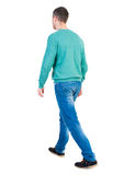 Back view of going  handsome man in jeans and a shirt. Royalty Free Stock Image