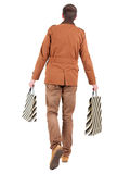 Back view of going  handsome man with shopping bags. Royalty Free Stock Image