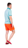 Back view of going handsome man in shorts. walking young guy stock image