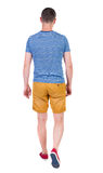Back view of going  handsome man in shorts.  walking young guy Stock Photography