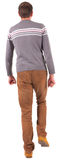 Back view of going   man in sweater and brown jeans. Royalty Free Stock Images