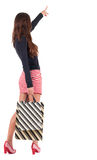 Back view of going  woman  in  dress  with shopping bags pointin Royalty Free Stock Images