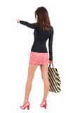Back view of going  woman  in  dress  with shopping bags pointin Royalty Free Stock Photography