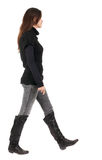 Back view of going  woman  in jeans and sweater Royalty Free Stock Images