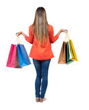Back view of going  woman  in  jeans woman with shopping bags . Stock Photos