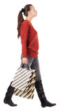 Back view of going  woman with shopping bags. Royalty Free Stock Image