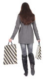 Back view of going  woman with shopping bags. Back view of going  woman  with shopping bags. beautiful brunette girl in gray coat bought Christmas presents Royalty Free Stock Image