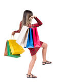 Back view of going  woman  with shopping bags . beautiful girl i Royalty Free Stock Photo