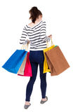 Back view of going  woman  with shopping bags . beautiful girl i Stock Photography