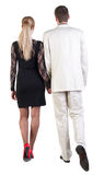 Back view of going young business couple (man and woman) . Stock Photo