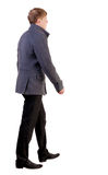 Back view of going  handsome business man in coat. Stock Photos