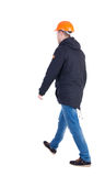 Back view of goingWorker in a helmet. walking young engineer. Royalty Free Stock Photo
