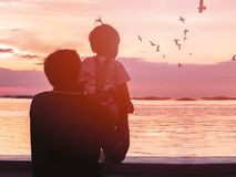 Grandfather and his niece looking at seagull birds royalty free stock images