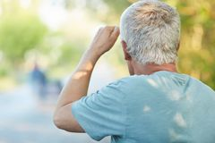 Back view of grey haired senior male looks into distnace, notices someone on road, has walk alone in countryside, likes to observe Stock Image
